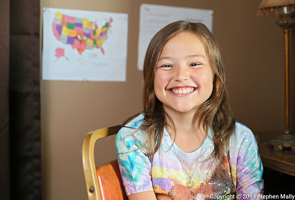 "Raegan Junge, 8, of Keystone at her desk in her ""office"" at her house in Keystone on Wednesday, July 17, 2013. Behind Junge is a map with pins in the various states she has helped over the past two years."
