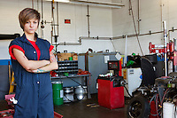 Portrait of a confident young female mechanic with arms crossed in garage