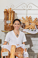 Portrait of woman in bakery with fresh breads