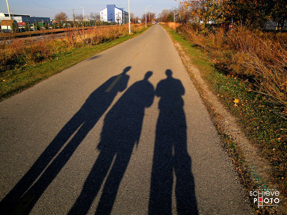Late afternoon shadows of three guys on the bike path.