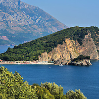 """St. Nikola's Island Near Budva, Montenegro<br /> It is easy to see how St. Nikola's Island got its nickname """"Školj"""" because it looks like a shell. This forested islet is about a mile wide and peaks at 397 feet. It sits majestically off the shore of Budva. During the summer, Sveti Nikola is very popular for its 2,755 (bare) feet of sandy beaches including the Beach of Paradise."""