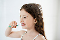 Girl Brushing Teeth in bathroom close up