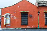 A brightly painted colonnaded style building along the Plaza Zaragoza in Tlacotalpan, Veracruz, Mexico. The tiny town is painted a riot of colors and features well preserved colonial Caribbean architectural style dating from the mid-16th-century.