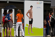 An image of French swimming champion Yannick Agnel  stands on an ad for energy corporation EDF, one of the Olympic sponsor partners in the Olympic Park during the London 2012 Olympics. Young women stand to admire him and have their photos next to his athletic figure outside the EDF corporate pavillion. EDF Energy has installed monitoring technology at sports venues across the Olympic park to show real-time energy consumption at the 2012 games. Agnel is a French swimmer and national record holder in the 200 and 400 m freestyle. Yannick Agnel (born June 9, 1992 in Nîmes) is a French swimmer and national record holder in the 200 and 400 m freestyle (long course). Agnel is also a nine-time medalist at the European Junior Swimming Championships. He has won two Olympic gold medals, both at the 2012 Summer Olympics.