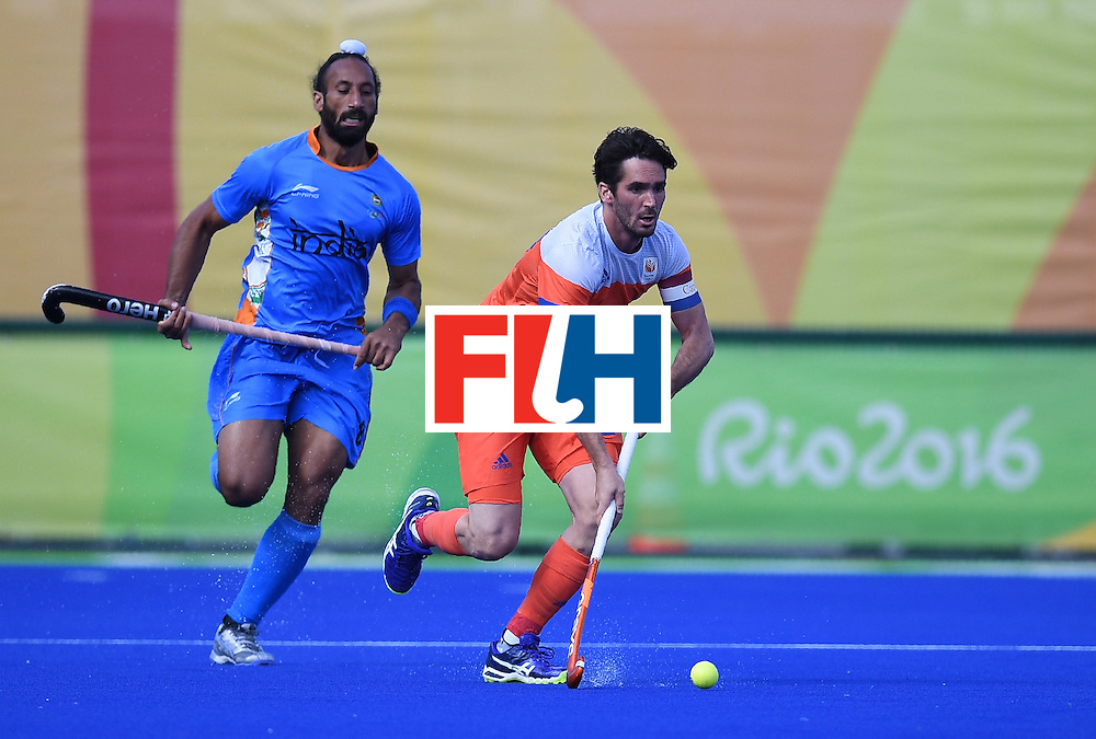 Netherland's Robert van der Horst controls the ball as India's Sardar Singh chases during the men's field hockey Netherland's vs India match of the Rio 2016 Olympics Games at the Olympic Hockey Centre in Rio de Janeiro on August, 11 2016. / AFP / MANAN VATSYAYANA        (Photo credit should read MANAN VATSYAYANA/AFP/Getty Images)