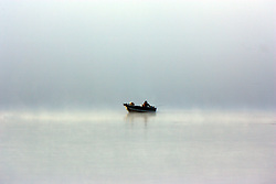 10 November 2007: Fisherman in a small boat in the fog on the lake. Comlara Park, McLean County, Illinois