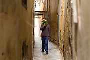 FEZ, MOROCCO - 3rd DECEMBER 2016 - Person walks through the old Fez Medina and smells fresh mint leaves bought from the food market, Morocco.