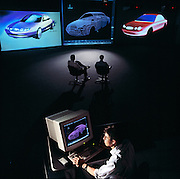 An engineer stylizes a new Taurus in Dearborn, Michigan while a design team analyzes the progress on a large screen monitor.  Using the digital techniques, the lag time from design to product has gone from years to weeks.