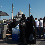 Turkey. Istambul. Eminonu area, urban life.  women with tchador Yeni Cami Mosque in the distance