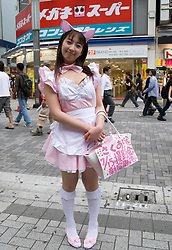 Young girl dressed in maids costume advertising nearby themed cafe in Akihabara Tokyo