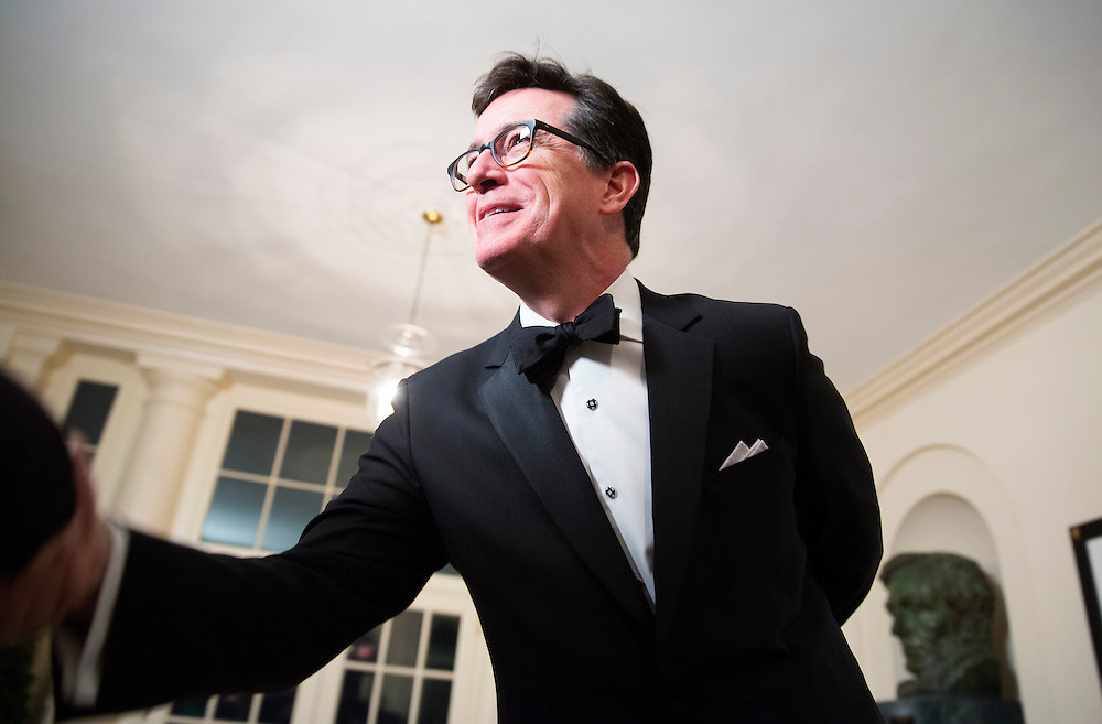Comedian Stephen Colbert greets a reporter as he arrives for the State Dinner being held for French President Francois Hollande at the White House in Washington on February 11, 2014.      REUTERS/Joshua Roberts    (UNITED STATES)