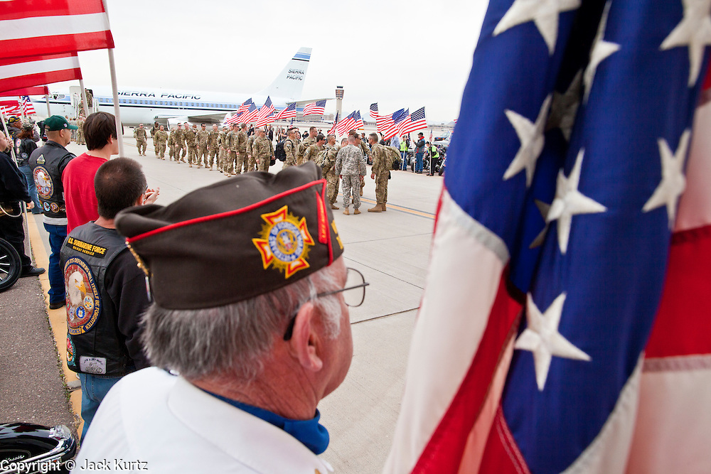 "15 JANUARY 2012 - PHOENIX, AZ:    A member of the VFW stands with a flag waiting as returing soldiers get in formation at the The 161st Air Refueling Wing of the Arizona Air National Guard in Phoenix. About 100 soldiers of A (Alpha) Company of the 422nd Expeditionary Signal Battalion (referred to as ""Alpha 4-2-2"") of the Arizona Army National Guard returned to Arizona on Sunday, Jan. 15, following a nearly year-long deployment to Afghanistan. More than 10,000 Arizona Army and Air National Guard Soldiers and Airmen have been ordered to federal active duty in support of Operations Noble Eagle, Enduring Freedom, Iraqi Freedom, and New Dawn since September 2001. Approximately 200 Arizona National Guard Soldiers and Airmen are still serving on federal active duty overseas.  PHOTO BY JACK KURTZ"