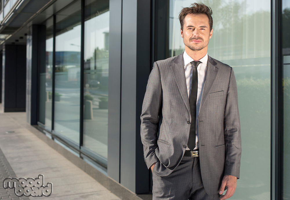 Portrait of handsome young businessman standing outside office building