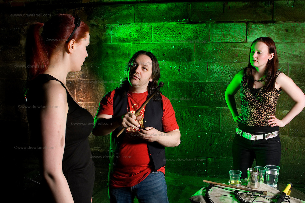Picture shows :  Writer Ailsa Longmuir  (in black) learns the Art of Fire Breathing / Fire Eating with her first  lesson from the Purple Productions team of Rufus T. Fahrenheit (tutor)  and fire Performer Lucille Burn (animal print)....Picture Drew Farrell Tel : 07721-735041.