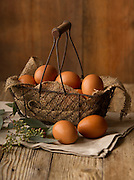 Still life photo of brown eggs on a rustic farm table, styled in a vintage basket