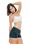 Young woman with beautiful slim body in crop top and hot pants on white background