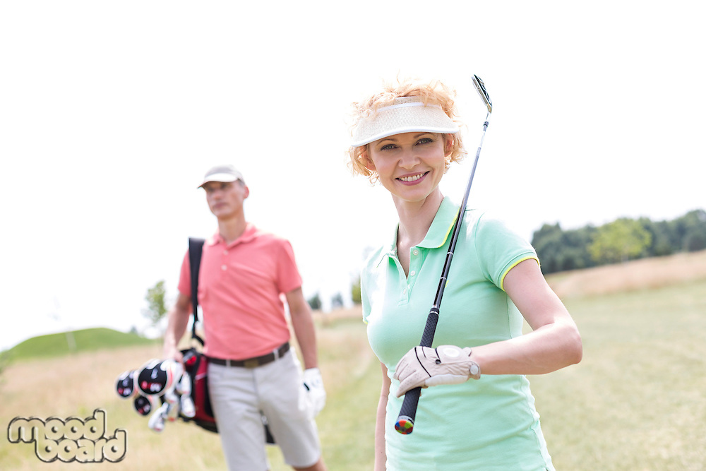 Portrait of happy female golfer with friend standing in background