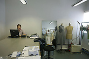 A garment tailor works with mannequins in the design studio at couturier Margaret Howell's Edmonton workshop factory