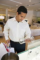 Man Examining Kitchenware in furniture store