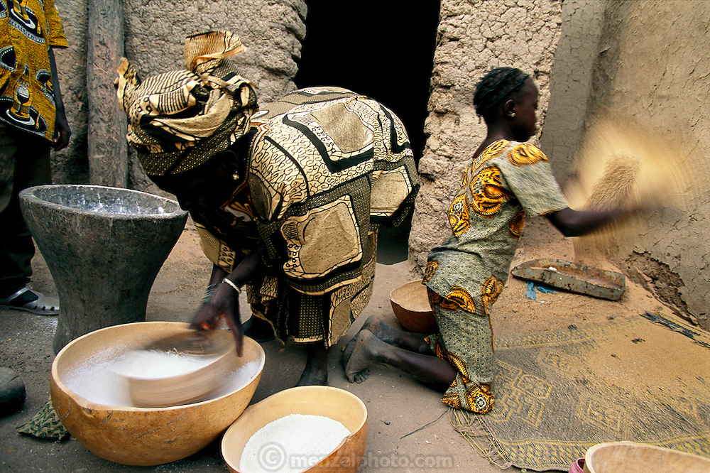 "(MODEL RELEASED IMAGE). After pounding rice into flour in a large wooden mortar, Pama Kondo sifts it to get rid of any remaining hulls. Behind her, 10-year-old Fatoumata (daughter of Fatoumata Toure, Pama's co-wife) does much the same with some sorghum. Can she foresee a day when she will no longer have to pound grain? ""That's what children are for,"" she replies seriously. Hungry Planet: What the World Eats (p. 212). The Natomo family of Kouakourou, Mali, is one of the thirty families featured, with a weeks' worth of food, in the book Hungry Planet: What the World Eats."
