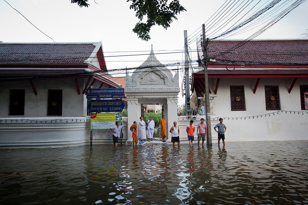 Prime Minister Yingluck Shinawatra told the crisis had now reached a critical point for Bangkok. The Chao Phraya River is already at record high level in places and many parts of the capital could be in danger by the weekend.///Residents stand outside the flooded street near Thammasat University.
