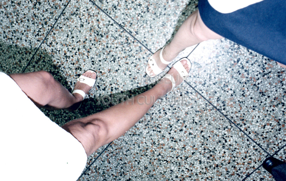 View of two women wearing white sandals and skirts.