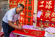 31 JANUARY 2014 - BANGKOK, THAILAND:   A calligrapher works on the Chareon Krung Street during Lunar New Year festivities, also know as Tet and Chinese New Year, in Bangkok. This year is the Year of the Horse. Ethnic Chinese make up about 14% of Thailand and Chinese holidays are widely celebrated in Thailand.     PHOTO BY JACK KURTZ