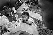 TUTTU, 5 Jahre alt, betrachtet aufmerksam, wie ein Mitarbeiter und eine Krankenschwester aus BAAN GERDA den Sirup auf eine Spritze aufgezogen hat und die Menge in der Spritze kontrolliert. ..Jedes der Kinder bekommt, abgestimmt auf sein Gewicht, eine bestimmte Menge an antiretroviraler Medizin..Auf dem Tisch liegen die verschiedenen Medikamente und die gereinigten Spritzen für Haus 1, GERDA HOUSE, in dem TUTTU mit sieben weiteren Kinder lebt. Provinz Lop Buri, Thailand...TUTTU, age 5, looks intensly how the medicine is prepared by an assistent. Checking dosage of the syringe filled with medicine..Every child gets his medicine cocktail, antiretroviral therapy, depenting on their weight. Fresh cleaned syringes and medicine for one week is laying on the table for House 1, where TUTTU lives with seven other children..Lop Buri, Thailand...