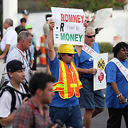 Protesters carry signs while marching in a parade during the Republican National Convention in Tampa, Fla. on Wednesday, August 29, 2012. (AP Photo/Alex Menendez)