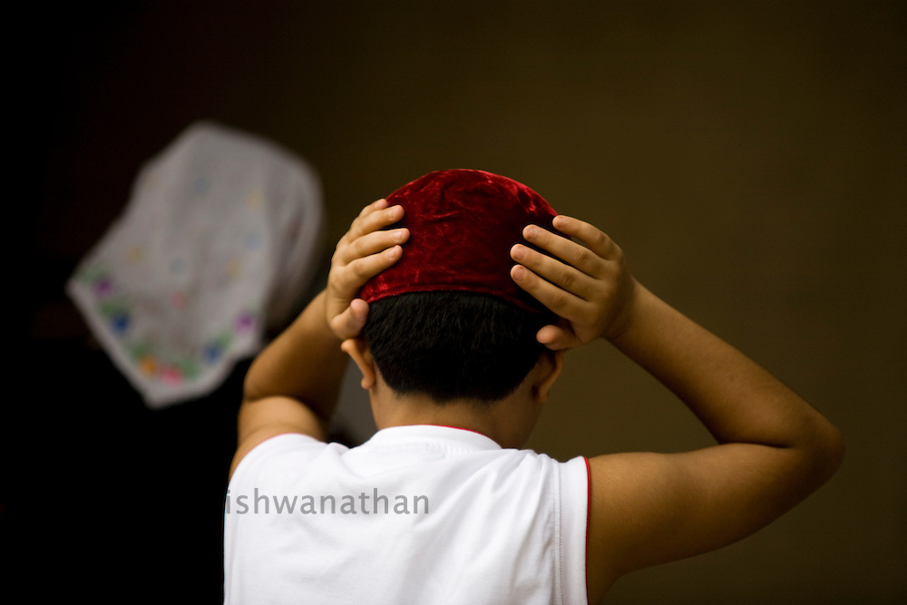 A Parsi boy adjusts his cap as he enters the Kappawala Agiary, or Fire Temple, on Navroze, the Parsi new year, in Mumbai, India, Tuesday, Aug. 19, 2008. Parsis, also known as Zoroastrians, worship fire and are followers of the Bronze Age Persian prophet Zarathustra. According to estimates there are only 150,000 Zoroastrians in the world today and more than 80,000 live in India, mostly in Mumbai. Photographer:Prashanth Vishwanathan/Atlas Press