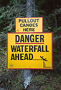 """Pull out canoes here - Danger ... Waterfall ahead"" sign at Bowron Lake Provincial Park, British Columbia, Canada. On the 73-mile Bowron canoeing trip, paddle a rectangular circuit of wilderness lakes and portage your canoe rolled on wheels. The Cariboo Mountains are the northernmost subrange of the Columbia Mountains."