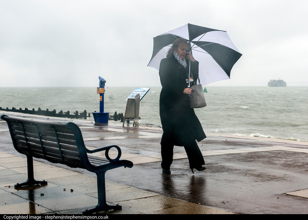 © Licensed to London News Pictures. 11/11/2014. Southsea, UK. A woman holds her umbrella against the strong wind on the seafront today.  Wet and windy weather today, 11 November 2014, at Southsea, Portsmouth. The Met Office have issued weather warnings in some parts of the UK. Photo credit : Stephen Simpson/LNP