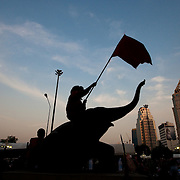 An anti-government protester waves a flag atop an elephant statue at a newly fortified barricade facing a Thai police line in Bangkok, Thailand, 20 April 2010. Tensions are mounting in the Thai capital as at least three five-star hotels in the Rachaprasong area closed 20 April, announcing plans to stay shut until 25 April, citing safety concerns as thousands of protesters continue to occupy the area and block it forcing hundreds of shops in the high end district to also stay closed. Hotel occupancy rates in the Thai capital have fallen dramatically in the last week as the protesters dig in and vow to remain until the current government led by Abhisit Vejjajiva steps down and calls new elections.