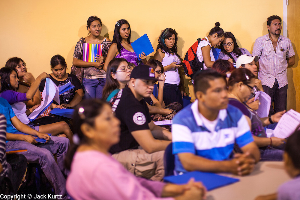 """18 AUGUST 2012 - PHOENIX, AZ:  People wait for a deferred action workshop to start in Phoenix. More than 1000 people attended a series of 90 minute workshops in Phoenix Saturday on the """"deferred action"""" announced by President Obama in June. Under the plan, young people brought to the US without papers, would under certain circumstances, not be subject to deportation. The plan mirrors some aspects the DREAM Act (acronym for Development, Relief, and Education for Alien Minors), that immigration advocates have sought for years. The workshops were sponsored by No DREAM Deferred Coalition.  PHOTO BY JACK KURTZ"""