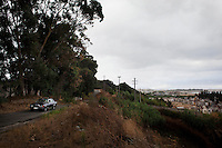Gioia Tauro, Italy - 1 September, 2012: A Mercedes passes by on a hill overlooking the cemetery of Gioia Tauro (right), by the port in in Gioia Tauro, a mafia stronghold in Italy, on September 1st, 2012. <br /> <br /> The current mayor of Gioia Tauro, Renato Bellofiore, was elected in 2010 after the former mayor and deputy mayor, Giorgio Dal Torrione and Rosario Schiavone, were arrested on Mafia charges in 2008. Both had been forced to step down when the city council was dissolved on suspicion of Mafia infiltration. Gioia Tauro is a city of 19,000 people built on an ancient Greek necrapolis and that today has the largest seaport in Italy and the sevent largest container port in Europe with its extension of 4,646 meters. Because the port is not connected to adeguate roads or rails, the ships mostly transfer containers to smaller vessels and little economic activity stays local. To authorities, the port is best known as the first point of entry for most of the cocaine that enters Europe from South America. In a routine rais earlier this month, authorities seized 176 kilos of pure cocaine with an estimated street value of 38 million euros.<br /> <br /> Calabria is one of the poorest Italian regions which suffers from lack of basic services (hospitals without proper equipment, irregular electricity and water), the product of disparate political interests vying for power. The region is dominated by the 'Ndrangheta (pronounced en-Drang-get-A), which authorities say is the most powerful in Italy because it is the welthiest and best organized.<br /> <br /> The region today has nearly 20 percent unemployment, 40 percent youth unemployment and among the lowest female unemployment and broadband Internet levels in Italy. Business suffer since poor infrastructure drives up transport costs.<br /> <br /> Last summer the European Union's anti-fraud office demanded that Italy redirect 380 million euros in structural funding away from the A3 Salerno - Reggio Calabria highway after finding widespread evidence of corruption in the b