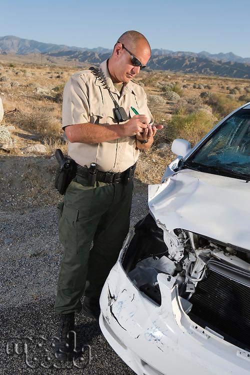 Police officer checking on damaged car