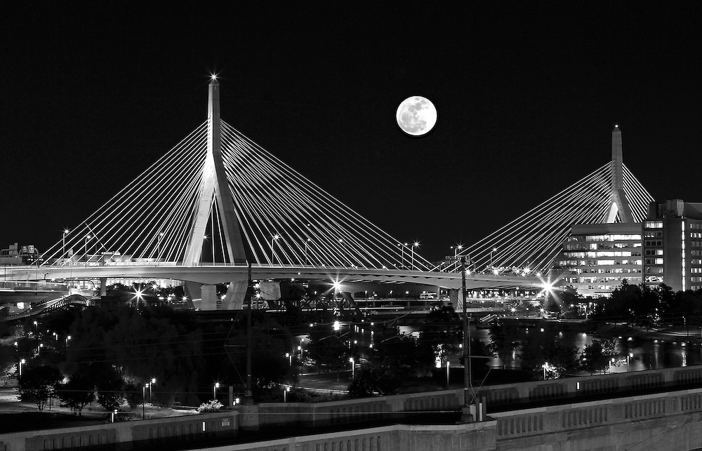 Black and White New England nature and astrology photography of a rising full moon over the historic Boston Bunker Hill Bridge in Charlestown, MA. This iconic bridge is better known as the Zakim Bridge that was erected as part of the Big Dig. It is always a special treat experiencing and photographing a full moon.<br />