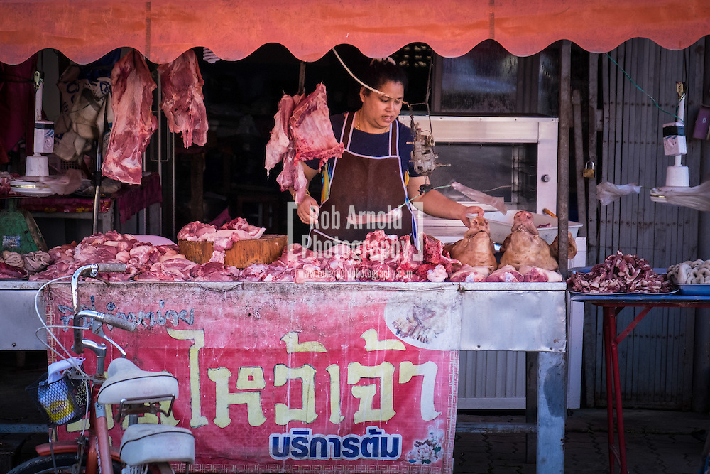 A woman selling meat from her street stall in Chiang Khong, Northern Thailand