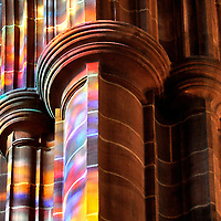 Column in the Liverpool Cathedral, Liverpool UK, with the colours of the stained glass windows opposite projected upon it.
