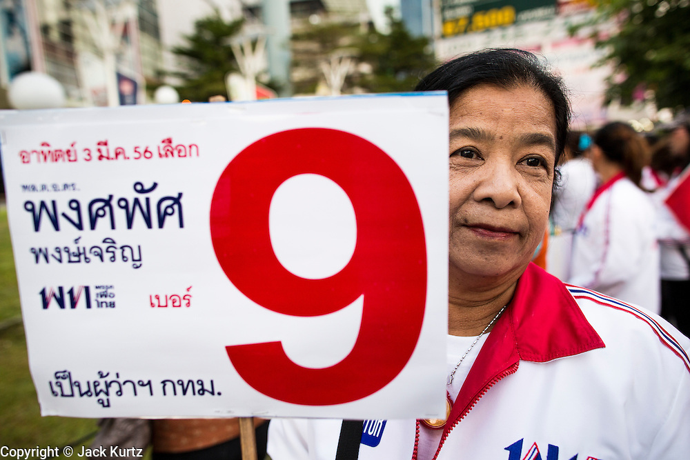 27 FEBRUARY 2013 - BANGKOK, THAILAND:  A woman waits for Pongsapat Pongchareon to arrive at one of his campaign rallies in Bangkok. Police General Pongsapat Pongcharoen (retired), a former deputy national police chief who also served as secretary-general of the Narcotics Control Board is the Pheu Thai Party candidate in the upcoming Bangkok governor's election. (He resigned from the police force to run for Governor.) Former Prime Minister Thaksin Shinawatra reportedly personally recruited Pongsapat. Most of Thailand's reputable polls have reported that Pongsapat is leading in the race and likely to defeat Sukhumbhand Paribatra, the Thai Democrats' candidate and incumbent. The loss of Bangkok would be a serious blow to the Democrats, whose base is the Bangkok area.    PHOTO BY JACK KURTZ