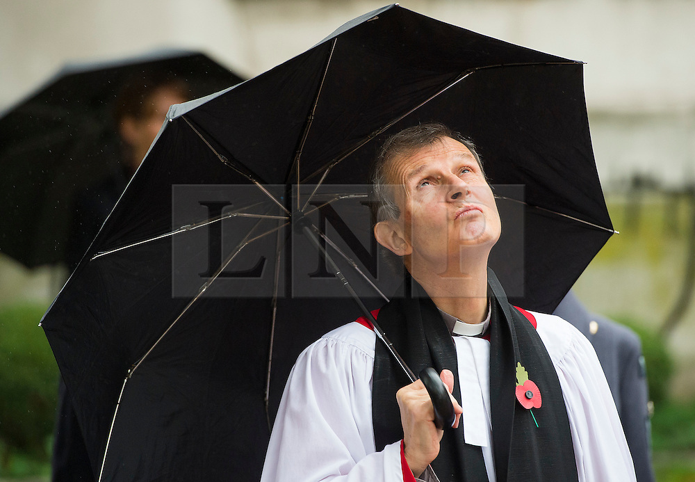 © Licensed to London News Pictures. 04/11/2015. London, UK. A clergymen sheltering from the rain underneath an umbrellas during the service. A service to mark the opening of the Filed of Remembrance at Westminster Abbey, attended by Prince Philip, Duke of Edinburgh and Prince Harry.  The Field of remembrance is a memorial garden to commemorate British and Commonwealth military and civilian servicemen and women in the two World Wars and later conflicts. Photo credit: Ben Cawthra/LNP