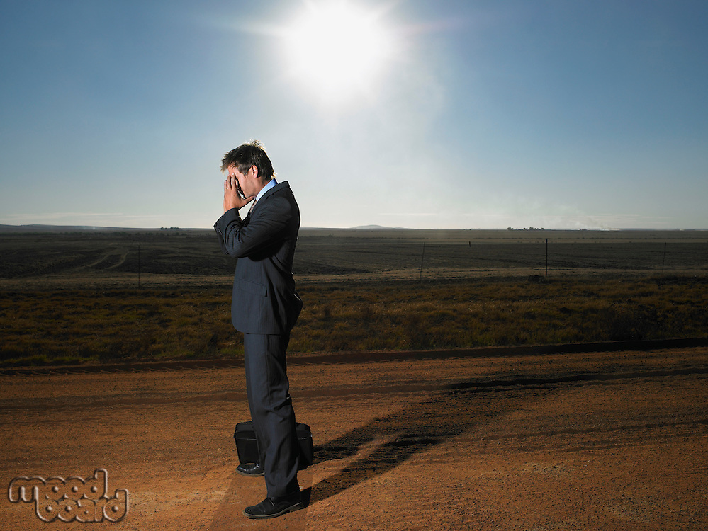 Frustrated businessman in middle of deserted road
