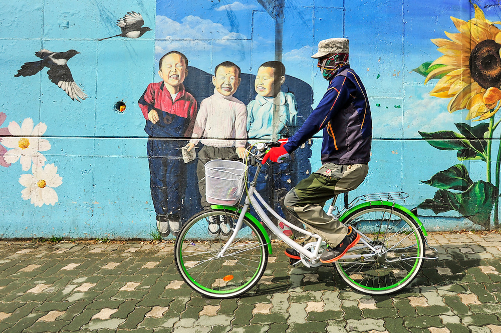 A man rides a bicycle past a mural near Gupo Market, a traditional market in Busan, South Korea.