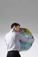 Young adult man with arms around big globe back view