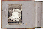 old and damaged photo album opening page with smiling toddler image
