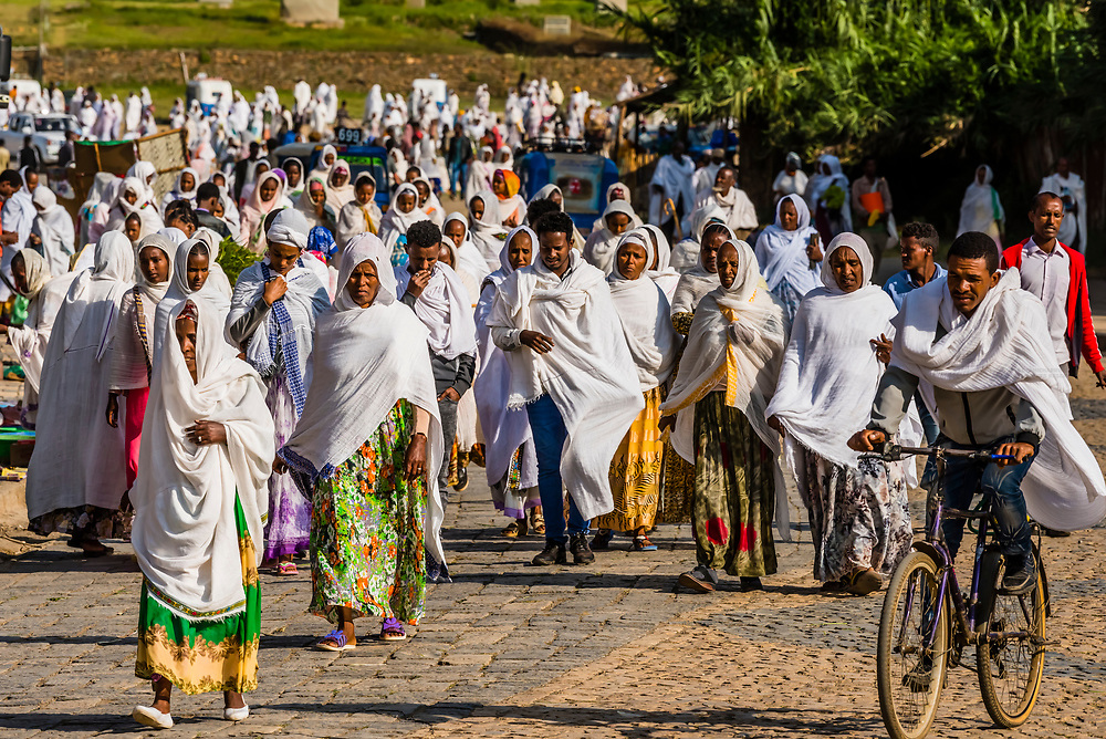 Crowds of people coming from prayer at the Church of Our Lady Mary of Zion, Axum (Aksum), Ethiopia. The Ethiopian Orthodox Tewahedo Church is said to contain the Ark of the Convenant. The women wear a white garment to prayer called a netela.