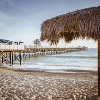 San Clemente pier and tiki umbrella retro photo. San Clemente is a popular beach city in Orange County Southern California in the States of America. Copyright ⓒ 2017 Paul Velgos with all rights reserved.
