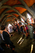 A crowd of people gathered inside an inflatable church, Boomtown, Matterley Estate, Alresford Road, Winchester, Hampshire, UK, August, 2010