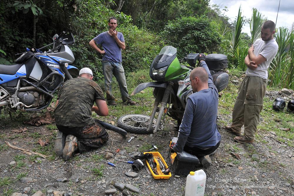 Repairing a flat on a motorcycle trip near Mapiri, Bolivia