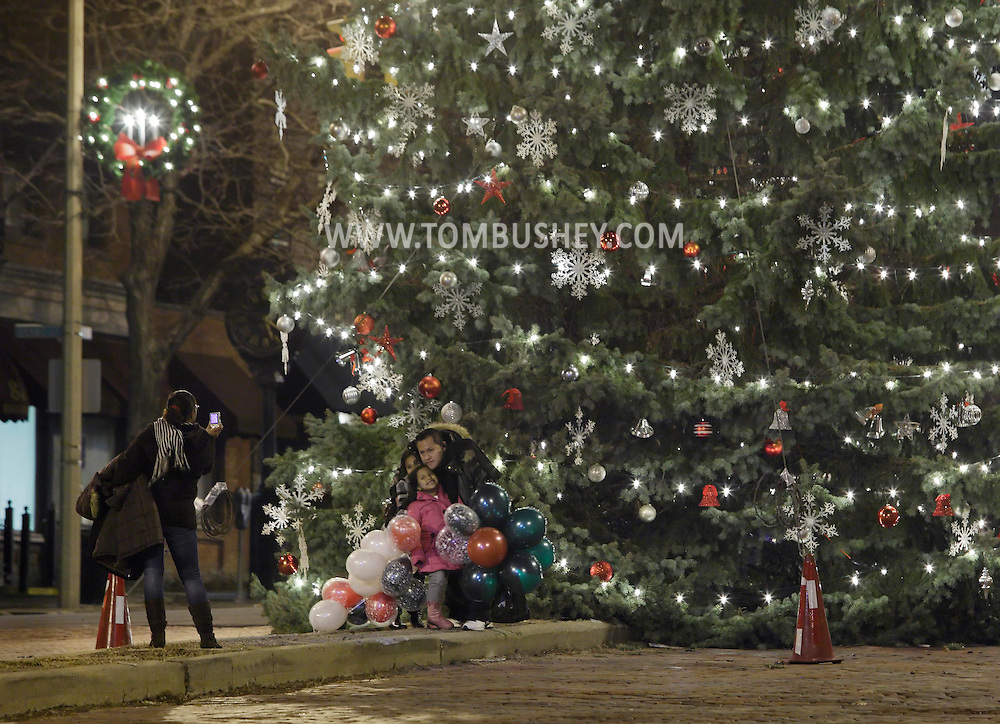 Newburgh, New York  - A family poses for photographs in front of the Christmas tree after the tree lighting ceremony on Broadway on the night of Dec. 14, 2011.
